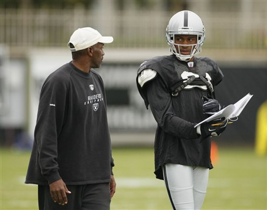 FILE - This Aug. 3, 2010, file photo shows Oakland Raiders cornerback Nnamdi Asomugha, right, reviewing a play book with defensive backs coach Lionel Washington during NFL football training camp in Napa, Calif.  Opposing teams spent much of last seasona avoiding Oakland star cornerback Nnamdi Asomugha. That's why this season the Raiders may try moving him around more often. (AP Photo/Eric Risberg, File)