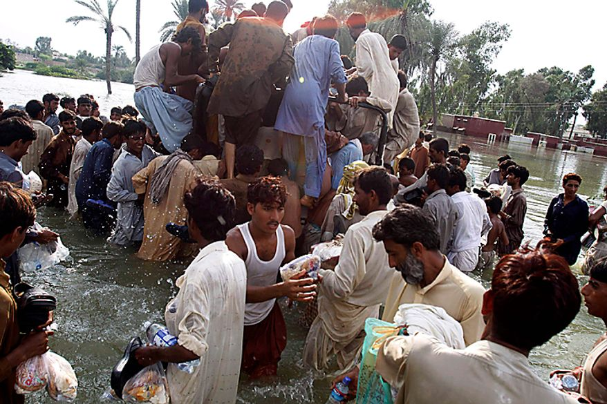 Flood survivors climb on a truck donating foods and drinks to victims along a flooded area in Muzaffargarh, Punjab province,  Pakistan on Wednesday Aug. 18, 2010. Militants exploiting the flooding chaos in Pakistan clashed with police overnight, authorities said, as desperately needed international donations for the millions of victims picked up pace three weeks after the deluge began. (AP Photo/Aaron Favila)