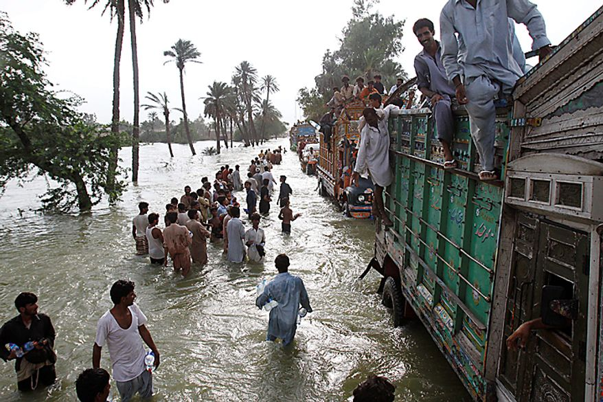 Flood survivors carry relief goods along a flooded area in Muzaffargarh, Punjab province, in Pakistan on Wednesday Aug. 18, 2010. Militants exploiting the flooding chaos in Pakistan clashed with police overnight, authorities said, as desperately needed international donations for the millions of victims picked up pace three weeks after the deluge began. (AP Photo / Aaron Favila)