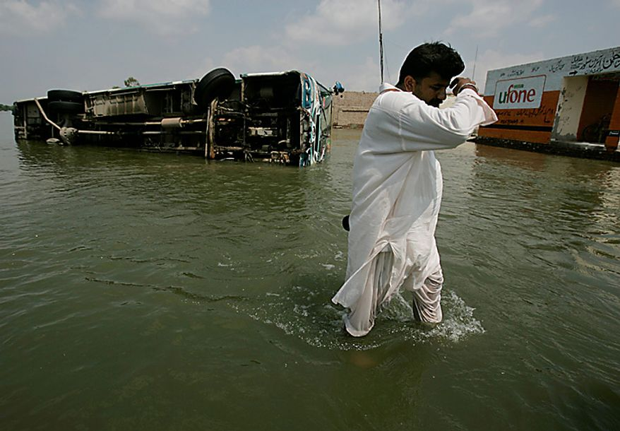 A Pakistani man passes by a toppled passenger bus along a flooded street  in Muzaffargarh, Punjab province,  Pakistan on Wednesday Aug. 18, 2010. Militants exploiting the flooding chaos in Pakistan clashed with police overnight, authorities said, as desperately needed international donations for the millions of victims picked up pace three weeks after the deluge began. (AP Photo/Aaron Favila)