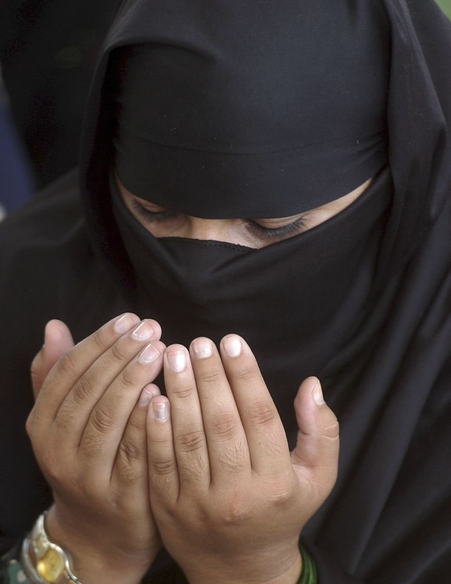 In this Oct. 22, 2004, file photo, a Pakistani woman prays after the first Friday prayers of the Islamic holy month of Ramadan at a mosque in Lahore, Pakistan. An Australian Muslim woman who sought permission to keep her face and head covered while she gives evidence at an upcoming trial was told by a judge Thursday, Aug. 19, 2010, she would have to remove her veil. (AP Photo/K.M. Chaudary, File)