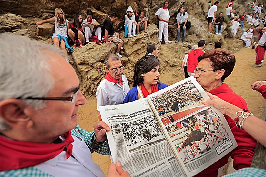 People read a local newspaper during the annual El Pilon bull run in Falces,  northern Spain, Thursday Aug. 19, 2010. The paper tells of 40 people injured Wednesday in nearby Tafalla, in the northern region of Navarra, when a bull leapt over a fence at a bullfight and climbed up the stairs of the stands knocking over people, including young children. The incident comes at a time when the country is split over whether bullfighting should be completely outlawed. (AP Photo/Alvaro Barrientos)