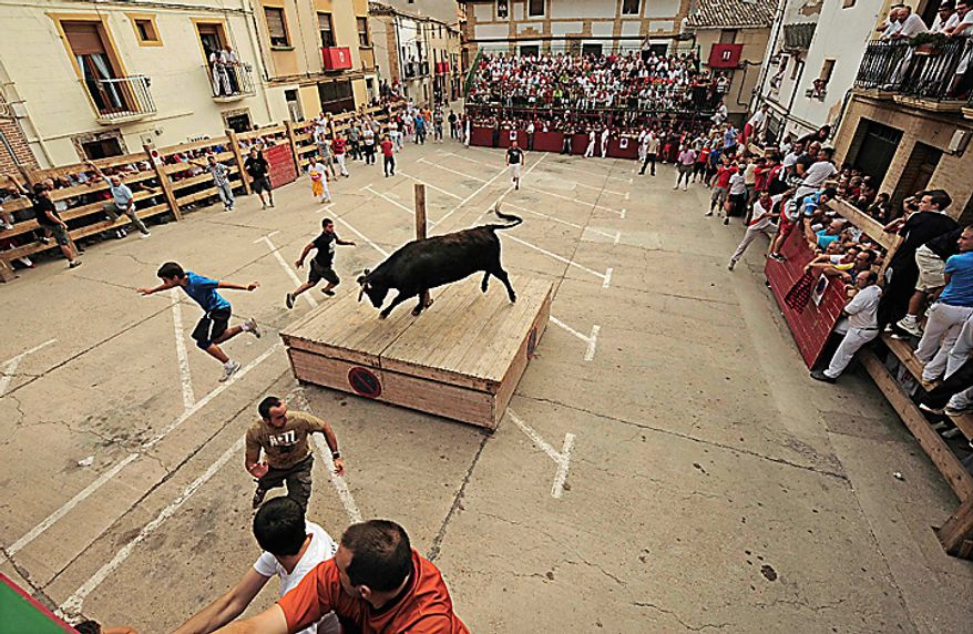 People dodge a bull in the town square during the annual El Pilon bull run in Falces, northern Spain, Thursday Aug. 19, 2010. Regional officials say 40 people were injured Wednesday in nearby Tafalla, in the northern region of Navarra, when a bull leapt over a fence at a bullfight and climbed up the stairs of the stands knocking over people, including young children. The incident comes at a time when the country is split over whether bullfighting should be completely outlawed. (AP Photo/Alvaro Barrientos)