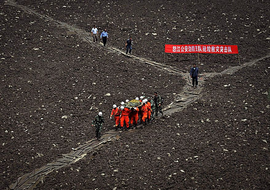 Rescuers move a victim's body after a landslide hit Gongshan county in southwest China's Yunnan province, Thursday, Aug. 19, 2010. China struggled to cope with widespread storms that left dozens missing and presumed dead Thursday as rescuers cleaned up a mudslide-stricken town, while two passenger train cars plunged into a river after crossing a flood-damaged bridge. (AP Photo)