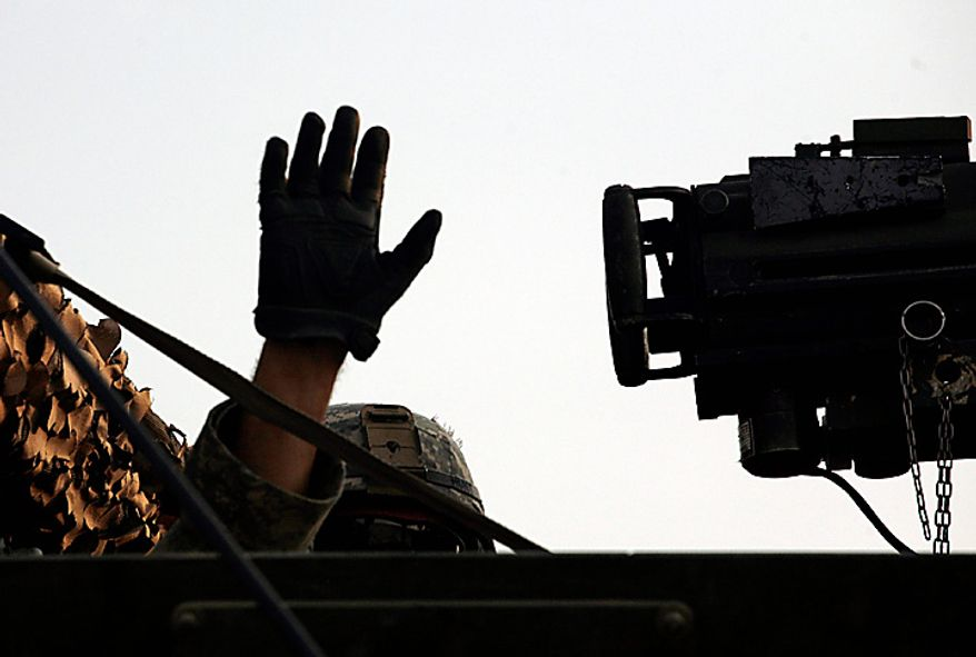 A U.S. Army soldier from 2nd Battalion, 23rd Infantry Regiment, 4th Brigade, 2nd Infantry Division waves from his Stryker armored vehicle after crossing the border from Iraq into Kuwait Wednesday, Aug. 18, 2010. The soldiers are part of the last combat brigade to leave Iraq as part of the drawdown of U.S. forces. (AP Photo/ Maya Alleruzzo)