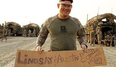 In this Aug. 16, 2010 photo, U.S. Army Staff Sgt. Jackie Vanover, from Spanaway, Wash. holds a hand-made message for his family, including his two-month-old daughter, Austin, after crossing the border from Iraq into Kuwait. Staff Sgt. Vanover, of 4th Battalion, 9th Infantry Regiment, 4th Brigade, 2nd Infantry Division, is in the last combat brigade to leave Iraq as part of the drawdown of U.S. forces. (AP Photo/ Maya Alleruzzo)