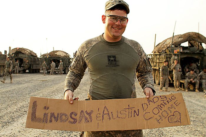 In this Aug. 16, 2010 photo, U.S. Army Staff Sgt. Jackie Vanover, from Spanaway, Wash. holds a hand-made message for his family, including his two-month-old daughter, Austin, after crossing the border from Iraq into Kuwait. Staff Sgt. Vanover, of 4th Battalion, 9th Infantry Regiment, 4th Brigade, 2nd Infantry Division, is