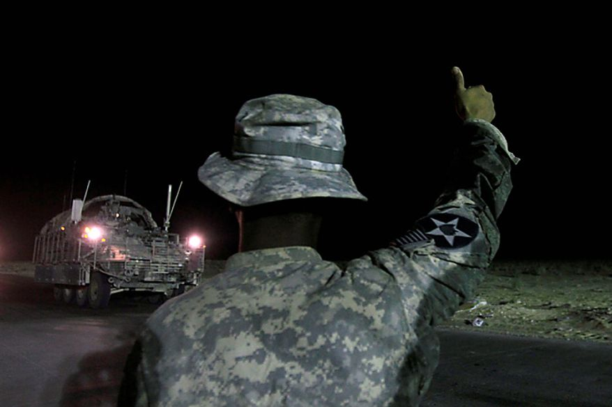 U.S. Army Spc. Luisito Brooks gives a thumbs-up to the last Stryker armored vehicle of the 4th Brigade to leave Iraq, as it crosses the border into Kuwait at the Khabari border crossing, Thursday, Aug. 19, 2010. The U.S. Army's 4th Brigade, 2nd Infantry Division is the last combat brigade to leave Iraq as part of the drawdown of U.S. forces.  (AP Photo/ Maya Alleruzzo)