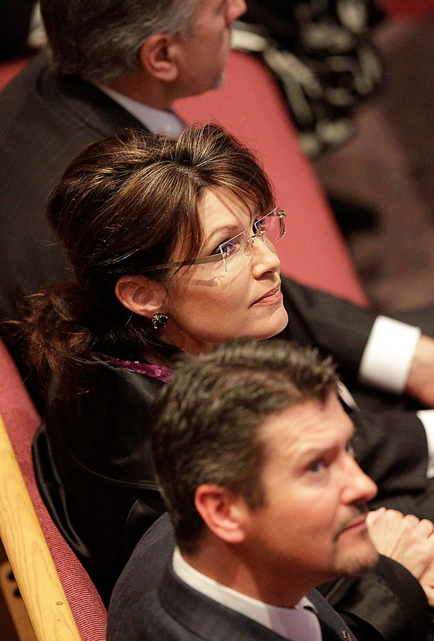 Former Alaska Gov. Sarah Palin and her husband Todd, look on during funeral services for former U.S. Sen. Ted Stevens at  the Anchorage Baptist Temple Wednesday, Aug. 18, 2010, in Anchorage, Alaska.  (AP Photo/Rick Bowmer)