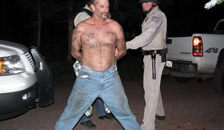 In this image provided by the U.S. Marshals Service fugitive John McCluskey is shown being taken into custody Thursday, Aug. 19, 2010, by U.S. Marshals in eastern Arizona. McCluskey and his fiancee Casslyn Welch have been on the lam since July 30th. Both were apprehended at an eastern Arizona campground on the Apache-Sitgreaves National Fores (AP Photo/U.S. Marshals Office)