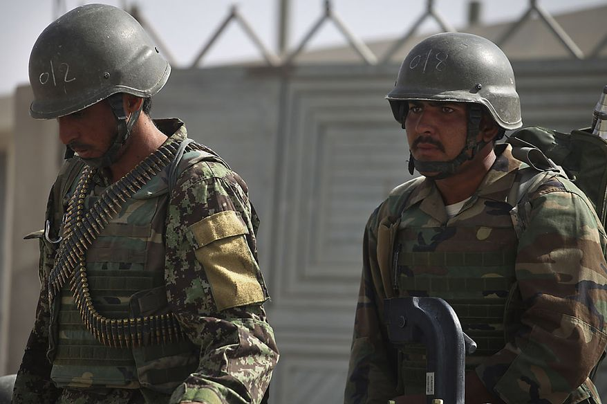 Afghan Army soldiers pictured during a lull in a battle outside the wire at the Afghan and U.S. Forward Operating Base Howz-e-Madad, operated by the U.S. 2nd Battalion, 502nd Infantry Regiment of the 101st Airborne Division, in Zhari district, Kandahar province, southern Afghanistan, Friday, Aug. 20, 2010. The 101st Airborne's 2-502 and their Afghan Army partners operate in a district which, as the birthplace of the Taliban movement, continues to hold many well-armed fighters, and a support network which provides the fighters with improvised explosives and safe havens. (AP Photo/Brennan Linsley)