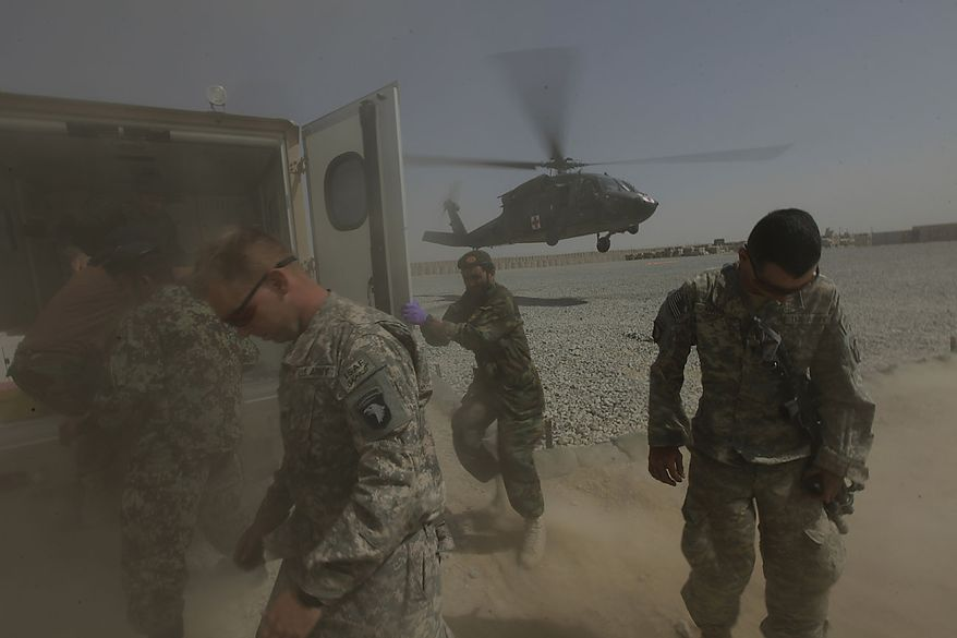 American and Afghan soldiers turn away from the dusty rotor wash as an Afghan soldier and police officer wounded in an ongoing firefight are evacuated by a U.S. Army, 101st Airborne Division, Task Force Destiny medevac helicopter, at the Afghan and U.S. Forward Operating Base Howz-e-Madad, operated by the the 101st's 2nd Battalion, 502nd Infantry Regiment, in Zhari district, Kandahar province, southern Afghanistan, Friday, Aug. 20, 2010. The The 101st Airborne's 2-502 and their Afghan Army partners operate in a district which, as the birthplace of the Taliban movement, continues to hold many well-armed fighters, and a support network which provides the fighters with improvised explosives and safe havens. (AP Photo/Brennan Linsley)