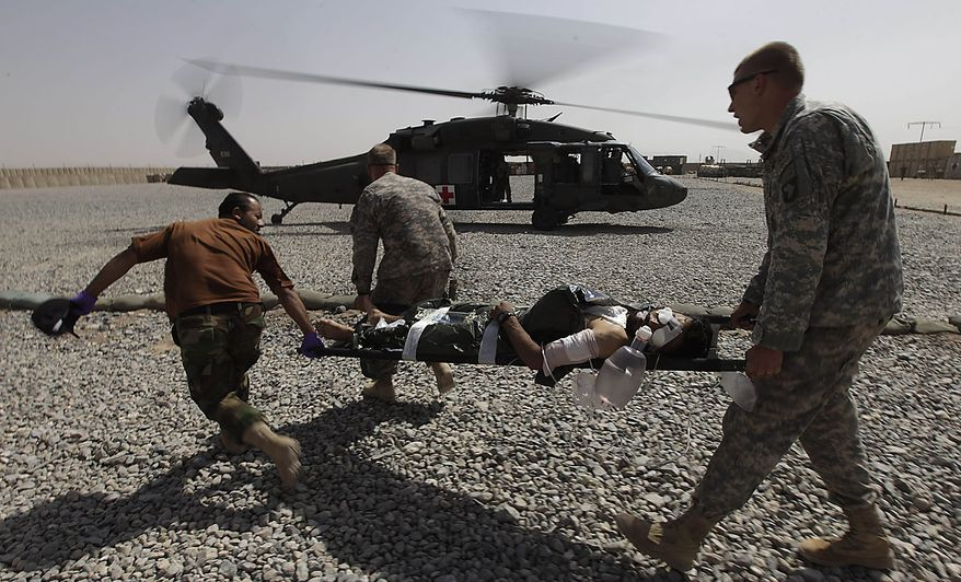 An Afghan soldier wounded in an ongoing firefight is loaded into a U.S. Army, 101st Airborne Division, Task Force Destiny medevac helicopter, at the Afghan and U.S. Forward Operating Base Howz-e-Madad, operated by the the 101st's 2nd Battalion, 502nd Infantry Regiment, in Zhari district, Kandahar province, southern Afghanistan, Friday, Aug. 20, 2010. The 101st Airborne's 2-502 and their Afghan Army partners operate in a district which, as the birthplace of the Taliban movement, continues to hold many well-armed fighters, and a support network which provides the fighters with improvised explosives and safe havens. (AP Photo/Brennan Linsley)