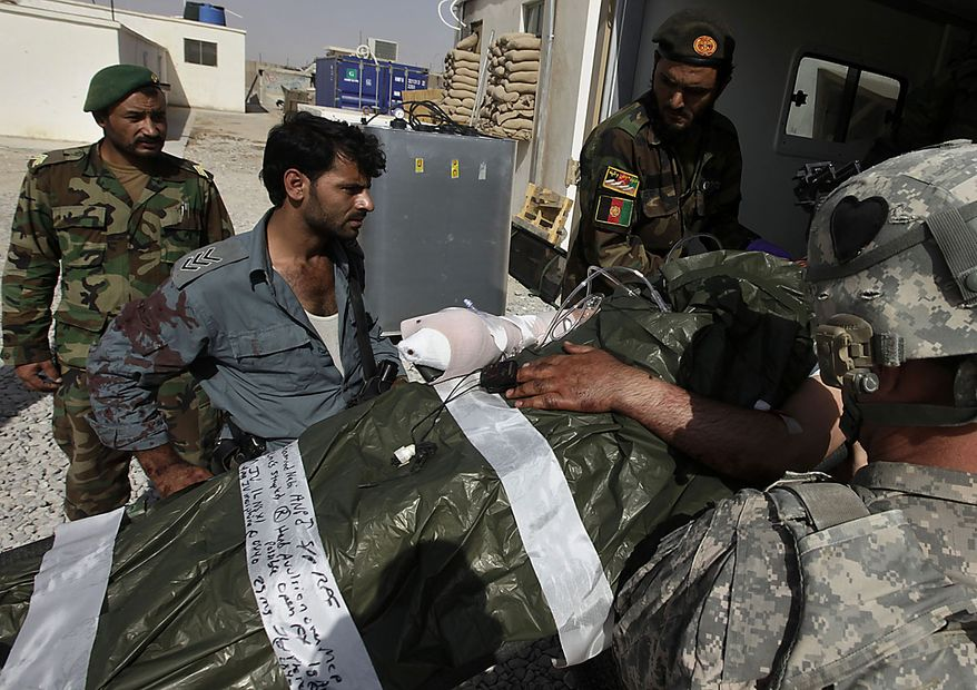 An Afghan National Police officer covered in the blood of his wounded comrade watches as he is loaded into an ambulance by U.S. Army medics and Afghan soldiers for transport to a helicopter landing zone, during an ongoing firefight outside the wire of the Afghan and U.S. Forward Operating Base Howz-e-Madad, operated by the 2nd Battalion, 502nd Infantry Regiment of the 101st Airborne Division, in Zhari district, Kandahar province, southern Afghanistan, Friday, Aug. 20, 2010. The 101st Airborne's 2-502 and their Afghan Army partners operate in a district which, as the birthplace of the Taliban movement, continues to hold many well-armed fighters, and a support network which provides the fighters with improvised explosives and safe havens. (AP Photo/Brennan Linsley)
