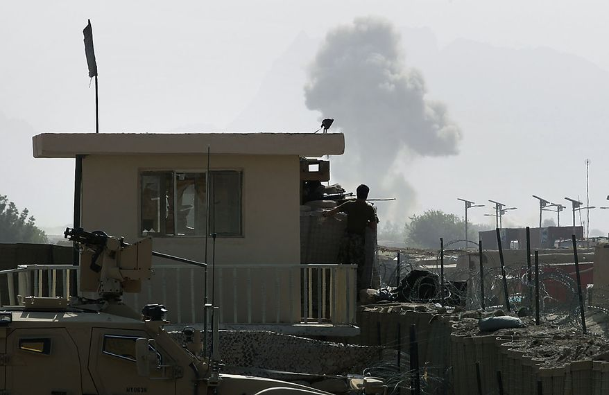 An Afghan Army soldier in a guard tower watches as an improvised explosive device blows up during a battle outside the wire at the Afghan and U.S. Forward Operating Base Howz-e-Madad, operated by the U.S. 2nd Battalion, 502nd Infantry Regiment of the 101st Airborne Division, in Zhari district, Kandahar province, southern Afghanistan, Friday, Aug. 20, 2010. The 101st Airborne's 2-502 and their Afghan Army partners operate in a district which, as the birthplace of the Taliban movement, continues to hold many well-armed fighters, and a support network which provides the fighters with improvised explosives and safe havens. (AP Photo/Brennan Linsley)