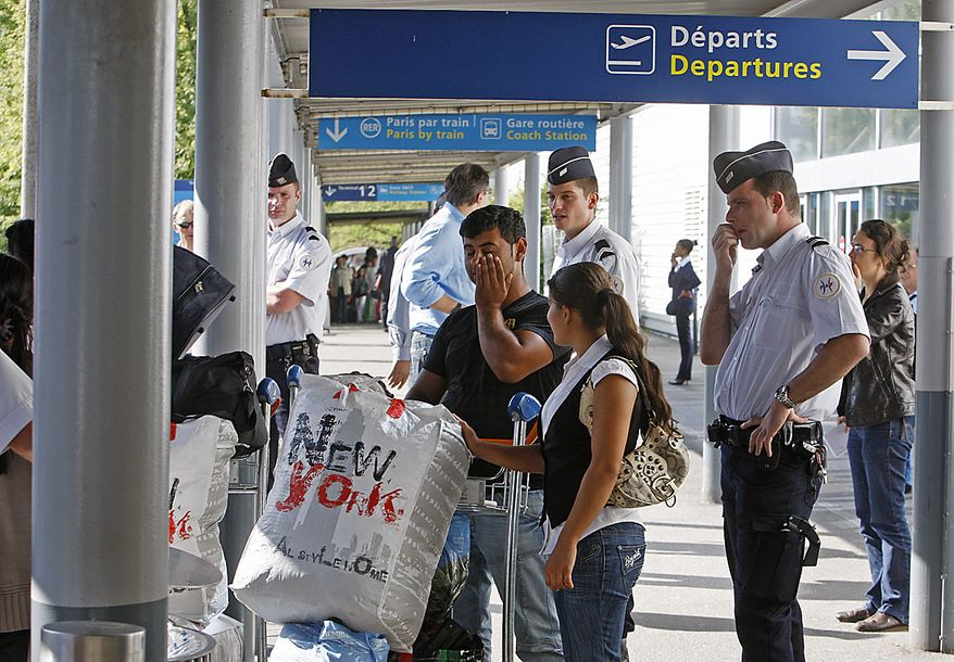 French police officers guards a Romnian Gypsy couple upon their arrival at Charles de Gaulle airport, near Paris , Friday, Aug. 20, 2010.  France has expelled nearly 139 Gypsy or Roma, from Paris's airport to their native Romania as part of a very public effort by conservative President Nicolas Sarkozy to dismantle Roma camps and sweep them out of the country. (AP Photo/Michel Euler)