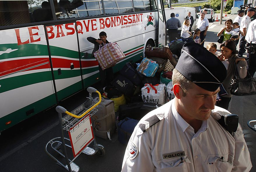 French police officers guard a bus carrying Romanian Gypsies en route to Romania at Roissy Charles de Gaulle airport, near Paris , Friday, Aug. 20, 2010.  France has expelled nearly 139 Gypsy or Roma, from Paris's airport to their native Romania as part of a very public effort by conservative President Nicolas Sarkozy to dismantle Roma camps and sweep them out of the country. (AP Photo/Michel Euler)