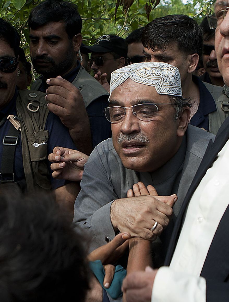 President of Pakistan Asif Ali Zardari, wears cap, listens the ordeal of flood survivors in Jampur near Dera Ghazi Khan in Pakistan on Thursday, Aug. 19, 2010. Islamist terrorists may exploit the chaos and misery caused by the floods in Pakistan to gain new recruits, the country's president said Thursday. Asif Ali Zardari's remarks were echoed by U.S. Sen. John Kerry, who toured some of the worst hit areas and visited a relief camp alongside the president. (AP Photo/B.K.Bangash)