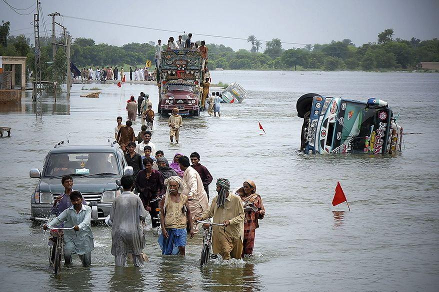 Flood survivors negotiate a flooded road at Muzaffargarh, in central Pakistan on Thursday, Aug. 19, 2010. The floods have affected 20 million people and about one-fifth of Pakistan's territory, straining its civilian government as it struggles against al-Qaida and Taliban violence. Aid groups and the United Nations have complained foreign donors have not been quick or generous enough given the scale of the disaster. (AP Photo/Khalid Tanveer)
