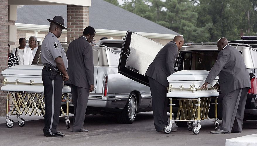 The caskets of Devean Duley and Ja'Van Duley arrive for the funeral Friday, Aug. 20, 2010, at St. Paul Baptist Church in Orangeburg, S.C. The boys' 29-year-old mother, Shaquan Duley, was not allowed to attend. Investigators say she confessed to smothering her children Sunday night then staging a car accident to cover up the deaths. (AP Photo/Mary Ann Chastain)