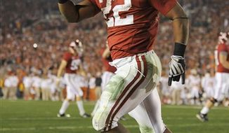 FILE - This Jan. 7, 2010, file photo shows Alabama running back Mark Ingram signaling to spectators after scoring a touchdown during the the fourth quarter of the BCS Championship NCAA college football game against Texas,  in Pasadena, Calif. The Alabama tailback is the latest Heisman Trophy winner trying to join Archie Griffin and collect a second. (AP Photo/Mark J. Terrill)