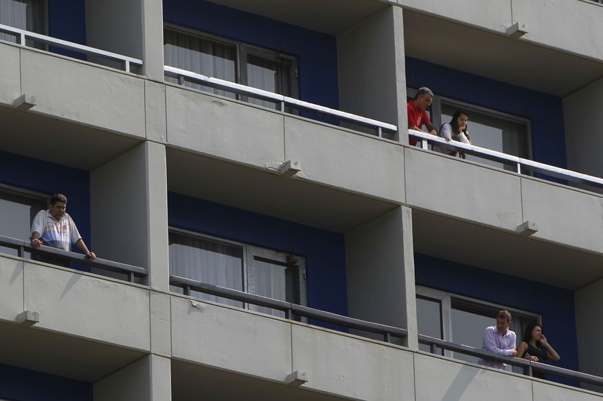 Tourists look from their balconies at the Intercontinental hotel after it was invaded by gunmen who took hostages in the Sao Conrado neighborhood near the Rocinha Slum in Rio de Janeiro, Brazil, Saturday Aug. 21, 2010. A police spokeswoman said that within a few hours the hostages were freed and the suspects surrendered. (AP Photo/Felipe Dana)