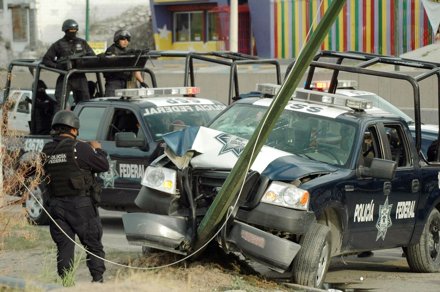 Federal police officers examine one of their vehicles after it crashed during a gunbattle in Ciudad Juarez, Mexico, on Saturday. At least one gunman was killed and three police officers were injured. (Associated Press)