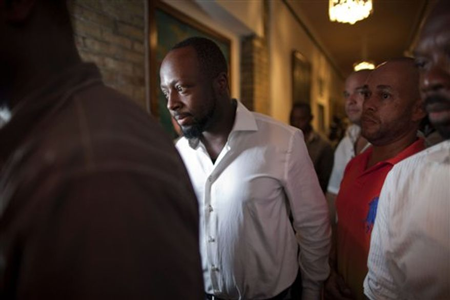 ** FILE ** Haitian-born singer and presidential candidate Wyclef Jean (second from left) walks surrounded by security after Haiti's Electoral Council rejected his candidacy in Port-au-Prince, Haiti, on Friday, Aug. 20, 2010. (AP Photo/Ramon Espinosa)
