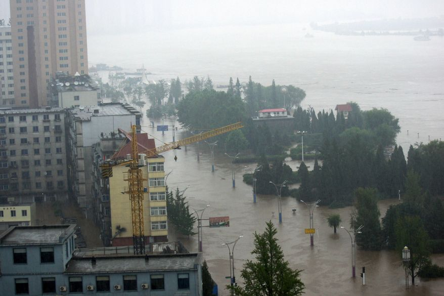 Roads along the Yalu River are inundated by floodwaters in Dandong in northeast China's Liaoning province on Saturday, Aug. 21, 2010. The Yalu, which marks China's border with North Korea, breached a dike Saturday after torrential rains, forcing the evacuation of more than 94,000 people. (AP Photos/Xinhua News Agency, Zhao Guiliang)