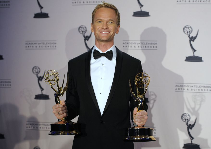 """Neil Patrick Harris poses with the Emmys he won as oustanding guest actor in a comedy series for """"Glee"""" and for oustanding special-class programs as the host at the 63rd annual Tony Awards at the Creative Arts Emmy Awards on Saturday, Aug. 21, 2010, in Los Angeles. (AP Photo/Chris Pizzello)"""