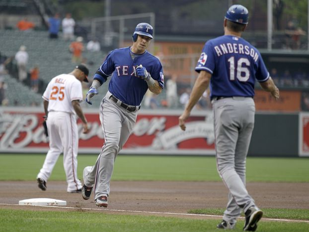 ASSOCIATED PRESS Texas Rangers third base coach Dave Anderson (16) waits to congratulate Josh Hamilton, center, who hit a three-run home run against the Baltimore Orioles during the first inning of a baseball game, Sunday, Aug. 22, 2010, in Baltimore. Orioles third baseman Josh Bell, left, looks on.