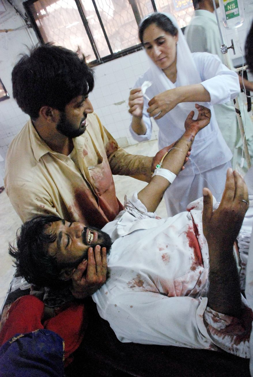 A Pakistani nurse treats a person injured by a bomb in Matni, at a local hospital in Peshawar, Pakistan, on Monday. (Associated Press)