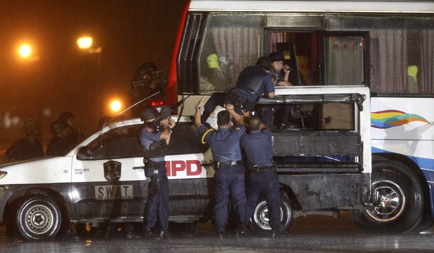 Police and SWAT members assault a tourist bus to rescue hostages at Manila's Rizal Park Monday, Aug. 23, 2010. Rolando Mendoza, a dismissed policeman armed with automatic rifle, seized the bus with 25 people aboard, mostly foreign tourists in a bid to demand reinstatement, police said. Mendoza was killed along with an undetermined number of hostages. (AP Photo/Bullit Marquez)