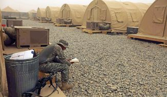 A U.S. soldier from the 101st Airborne Division reads as a sandstorm blows around him at Forward Operating Base Howz-e-Madad in southern Afghanistan's Zhari district on Tuesday. U.S. and Afghan troops plan an assault there, the birthplace of the Taliban, next month. (Associated Press)
