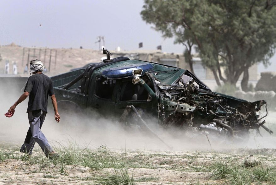 **FILE** An improvised explosive device (IED) wrecked a police car and wounded several police officers in Jalalabad, east of Kabul, Afghanistan, on Aug. 24, 2010. (Associated Press)