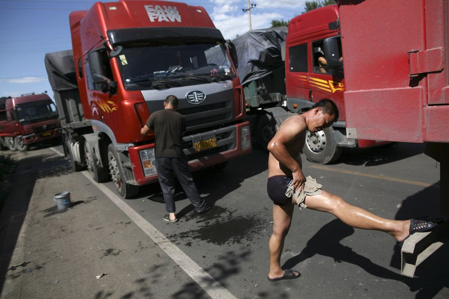 In this photo taken on Monday, Aug. 23, 2010, a truck driver washes himself after waiting over two days in the jam on an entrance ramp to the Beijing-Tibet Highway in Zhangbei county, in north China's Hebei province. The massive traffic jam that stretches for dozens of miles and hit its 10-day mark on Tuesday stems from road construction in Beijing that won't be finished until the middle of next month, an official said.
