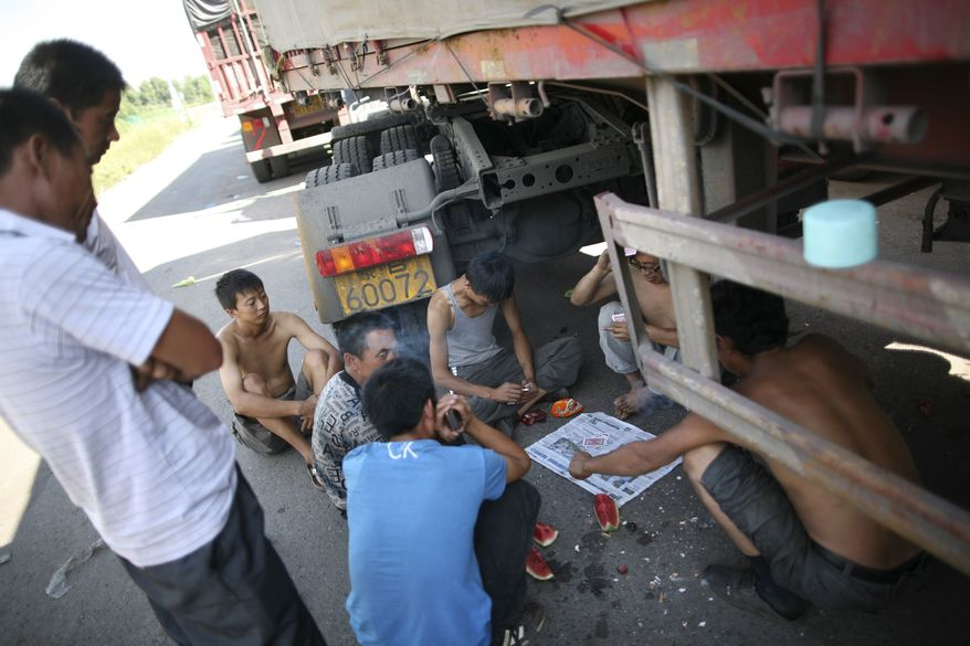 In this photo taken on Monday, Aug. 23, 2010, truck drivers play cards in the shade of a truck jammed on an entrance ramp to the Beijing-Tibet Highway in Guoleizhuang township, in north China's Hebei province. The massive traffic jam that stretches for dozens of miles and hit its 10-day mark on Tuesday stems from road construction in Beijing that won't be finished until the middle of next month, an official said. (AP Photo)