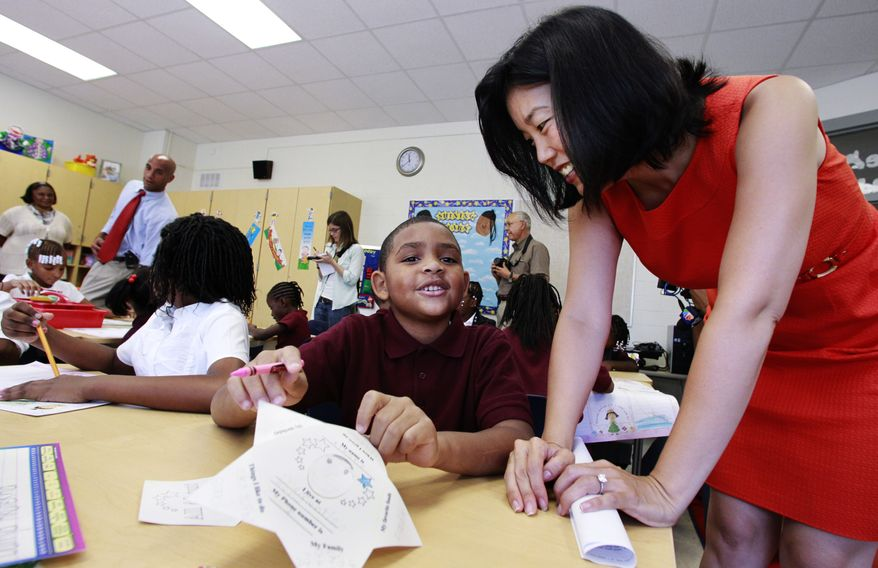 D.C. Public Schools Chancellor Michelle Rhee (right) talks with third-grader Kmone Feeling, who wants to be a librarian, during a visit to J.O. Wilson Elementary School in Northeast Washington on Monday, Aug. 23, 2010, the first day of the new academic year. D.C. Mayor Adrian M. Fenty (second from left) and Principal Sheryl Warley (left) stand at the back. (AP Photo/Manuel Balce Ceneta)