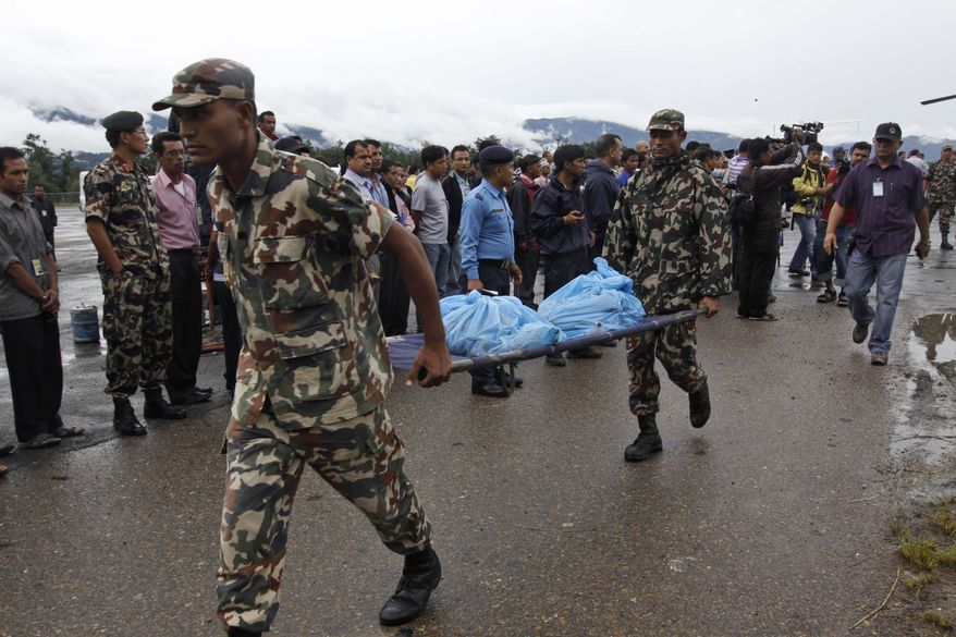 Nepalese soldiers carry the remains of plane crash victims in Katmandu, Nepal, Tuesday, Aug. 24, 2010. A small passenger plane heading to the Mount Everest region crashed in heavy rain Tuesday near Shikharpur village, about 50 miles south of Katmandu, killing all 14 people aboard, including four Americans, a Briton and a Japanese national, officials said. (AP Photo/Binod Joshi)
