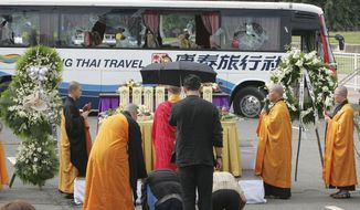 Relatives of the eight Hong Kong tourists who were killed in the tourist bus hostage crisis, kiss the ground near the bullet-riddled tourist bus during a Buddhist ceremony Tuesday, Aug. 24, 2010, at Rizal Park in Manila, Philippines. The Chinese authorities demanded answers from the Philippines on Tuesday after a 12-hour hostage drama in the heart of Manila ended with eight Hong Kong tourists and their Filipino hostage-taker dead following a day of botched negotiations. (AP Photo/Bullit Marquez)