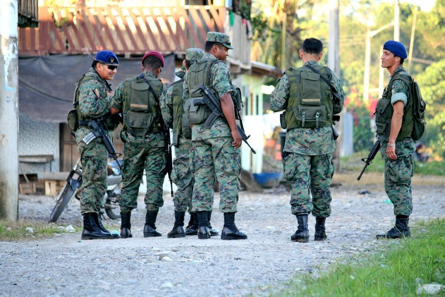 Ecuadorean soldiers patrol the town of Puerto Nuevo in Ecuador, made up primarily of Colombian refugees. Officials say the town is a haven for guerrillas fighting across the border in Colombia's civil war. (Kelly Hearn)