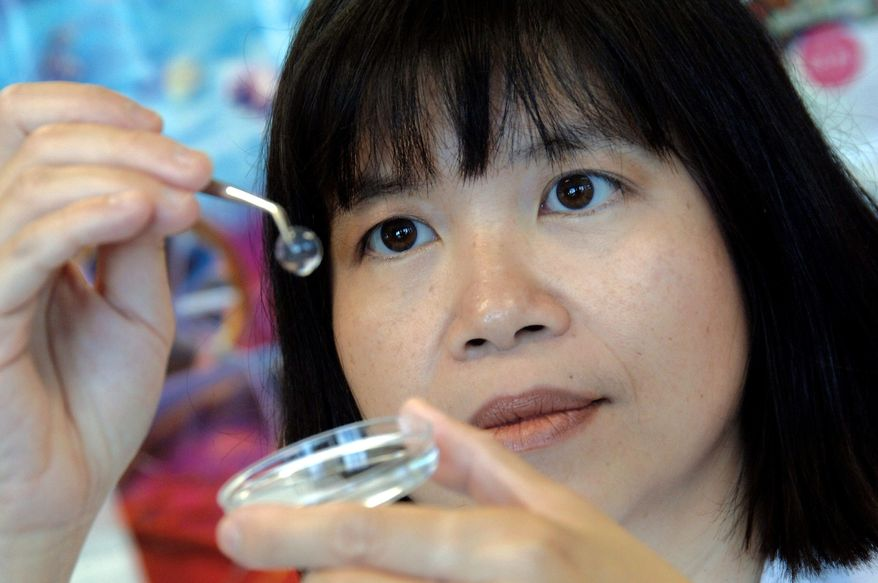 OTTAWA HOSPITAL RESEARCH INSTITUTE VIA ASSOCIATED PRESS Dr. May Griffith of the Ottawa Hospital Research Institute in Canada displays in 2005 a biosynthetic cornea that, implanted into the eye, coaxes the eye's natural corneal cells to regrow.