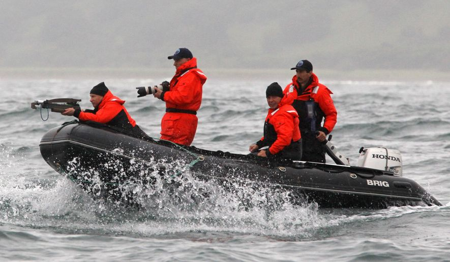 Russian Prime Minister Vladimir Putin aims a crossbow as he is on a rubber boat at the Olga Harbor of Kamchatka Peninsula during a scientific expedition, to study grey whales on Wednesday, Aug.25, 2010. (AP Photo/ RIA Novosti, Alexei Druzhinin, pool)