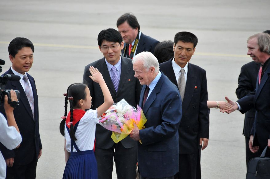 In this photo released by China's Xinhua News Agency, a child salutes former U.S. President Jimmy Carter, center, upon his arrival at the airport in Pyongyang, North Korea, on Wednesday, Aug. 25, 2010. Mr. Carter arrived in North Korea on Wednesday on a mission U.S. officials said was aimed at bringing home an imprisoned American. (AP Photo/Xinhua, Yao Ximeng)