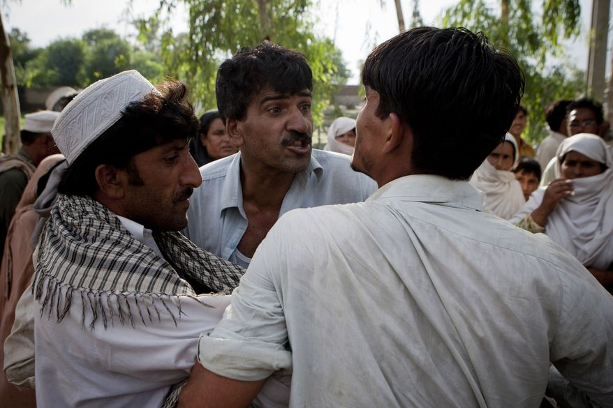 Pakistani flood victims fight over relief supplies taken from a truck carrying goods for distribution in Nowshera near Peshawar, Pakistan, on Wednesday, Aug. 25, 2010. (AP Photo/B.K. Bangash)