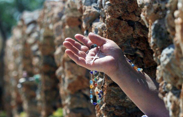 A woman holds up her rosary Thursday during a commemorative Mass in Vau I Dejes, Albania. Mother Teresa was of Albanian origin. The day began the Catholic Church's Year of Mother Teresa.
