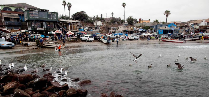 Fishermen and others gather at the beach in the fishing village of Popotla, Mexico, about 15 miles south of the U.S. border. Illegals are increasingly departing by sea from Popotla and elsewhere as land corridors are increasingly closed. (Associated Press)