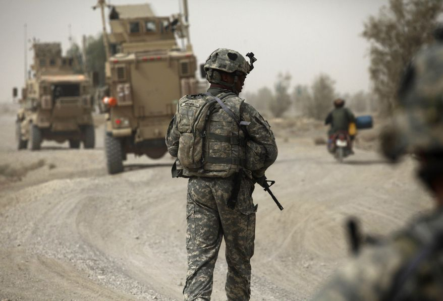 A U.S. Army soldier of the 101st Airborne Division walks along a road during a day of joint missions with the Afghan army in the Zhari district of Kandahar province in southern Afghanistan on Thursday, Aug. 26, 2010. (AP Photo/Brennan Linsley)