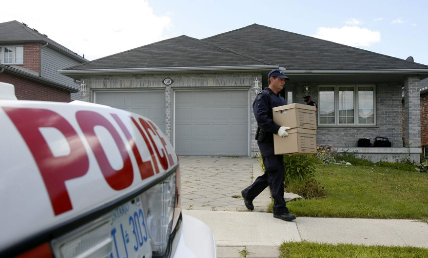 Royal Canadian Mounted Police investigators remove evidence boxes from a home in London, Ontario, Thursday, Aug. 26, 2010. A resident of the house was taken into custody earlier this morning. Police have charged three suspects in what police and court documents say was a terrorism plot that ranged from Canada to Iran, Afghanistan, Dubai and Pakistan. (AP Photo/The Canadian Press, Dave Chidley)
