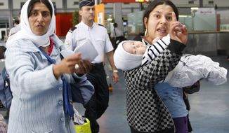 Roma women gesture before being expelled from France at Charles de Gaulle Airport northeast of Paris on Thursday, Aug. 26, 2010. (AP Photo/Jacques Brinon)